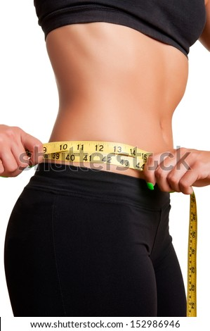 Woman measuring her waist with a yellow measuring tape, isolated in white - stock photo