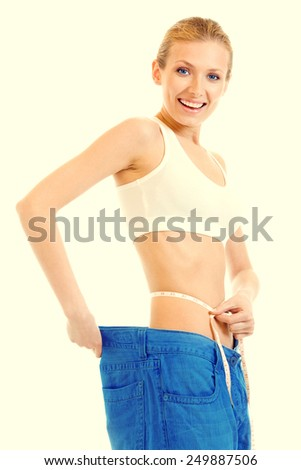 Woman measuring waist with a tape measure in old jeans - stock photo