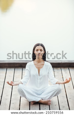 Woman mediating. Beautiful young woman in white clothing sitting in lotus position and keeping eyes closed while meditating outdoors - stock photo
