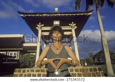Woman meditates at shrine in Buddhist Cemetery in Maui Hawaii