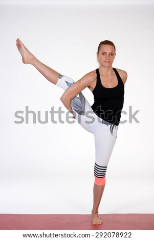Woman meditating and doing yoga excercise against white isolated studio background. - stock photo