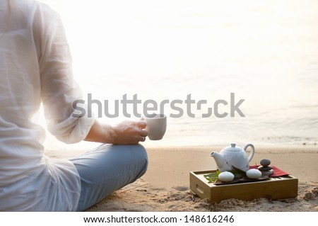 Woman meditating and drinking tea on beach - stock photo