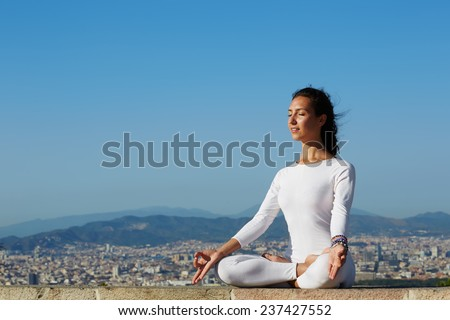 Woman meditating and exercising in yoga pose on high altitude, young woman seated in yoga pose on amazing city background , attractive girl makes yoga on mountain hill at sunset - stock photo