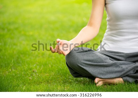 woman meditating and Yoga in a park  - stock photo