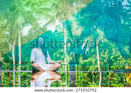 Woman meditating at pool side. Reflection in the water - stock photo