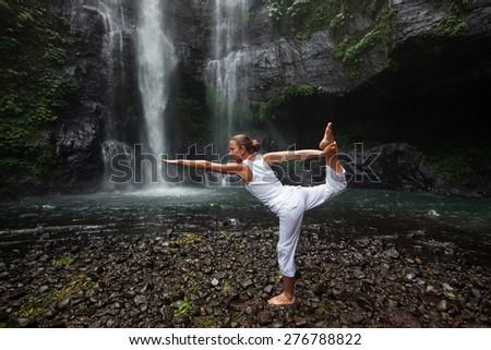 woman meditating doing yoga between waterfalls - stock photo