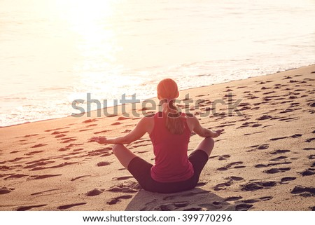 woman meditating in a yoga pose on beach - stock photo