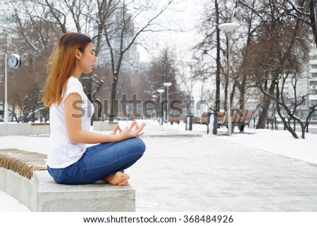 Woman meditating in The Park, Winter Time - stock photo