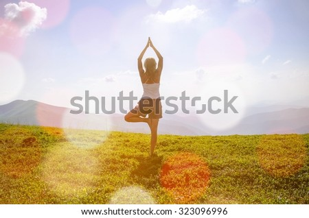 Woman meditating in tree yoga position on the top of a mountains at daylight. Zen, meditation, peace - stock photo