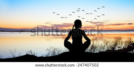 woman meditating on the lake - stock photo