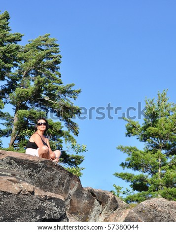 Woman meditating under a pine tree