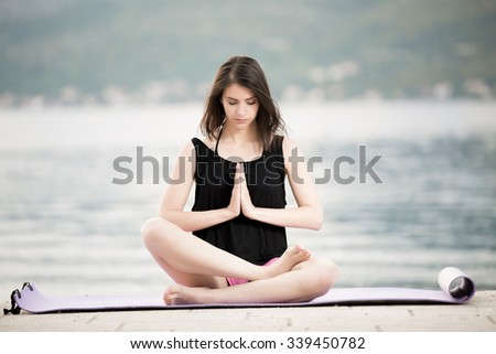 Woman meditating.Vacation vitality healthy living.Free woman embracing the sunshine,enjoying peace,serenity in nature.Beautiful fit female fitness woman practicing yoga.Summer body goals.Lotus pose - stock photo