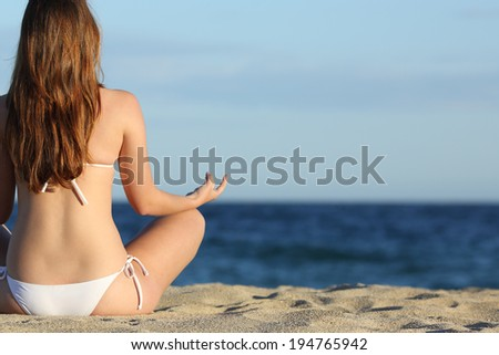 Woman meditating yoga on the beach in summer with the horizon over the sea in the background