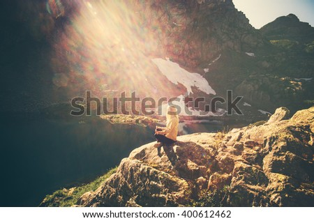 Woman meditating yoga sitting on cliff alone sun light Travel healthy Lifestyle concept lake and rocky mountains landscape on background outdoor  - stock photo
