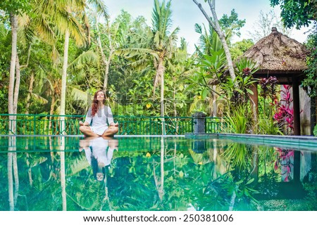 Woman meditation at gorgeous pool side of luxury tropical villa - stock photo