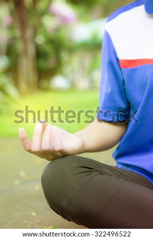 Woman meditation In the natural park with light meditation at hand - stock photo