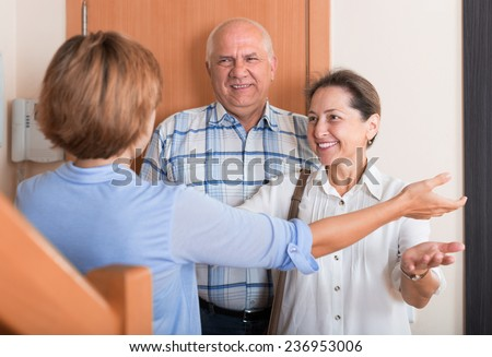 Woman meeting mature friends at the door - stock photo