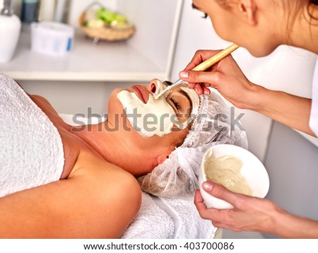 Woman middle-aged take facial and neck clay mask in spa salon. Eyes closed.