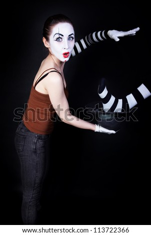Woman mime performing focus on a black background