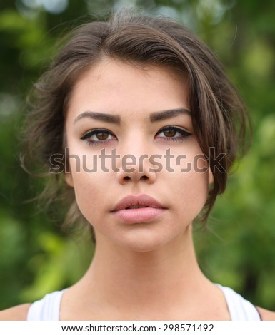 Woman model posing against green natural background. Soft focus om lips. - stock photo