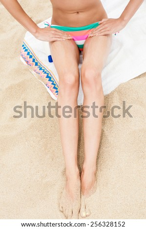 Woman moisturizing applying sun cream on her tanned body and legs. - stock photo
