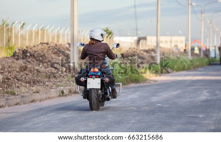 Woman motorcyclist driving on asphalt highway, rear view