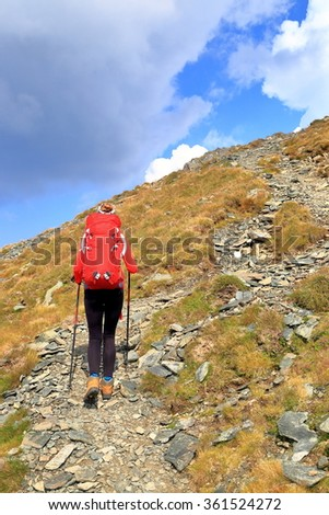 Woman mountaineer carries a red backpack on steep trail  - stock photo