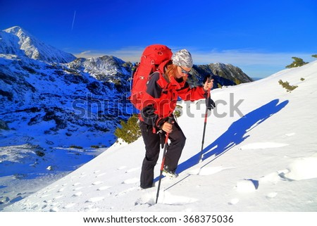Woman mountaineer carries a red backpack while climbing steep snowy route in Retezat mountains, Romania - stock photo