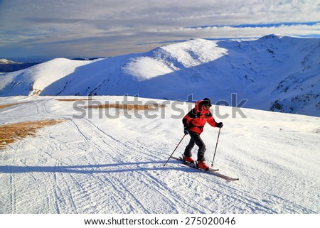Woman mountaineer climbing on touring skis above snow covered mountains - stock photo