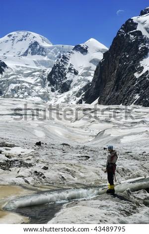 Woman mountaineer near glacial stream. Karator glacier. Kuylu mountains, Central Tien-Shan, Kyrgyzstan. - stock photo