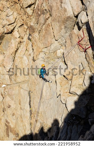 woman mountaineer rappelling down a mountain cliff - stock photo