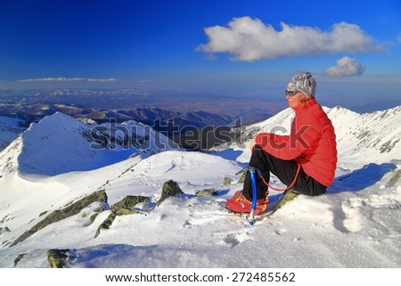 Woman mountaineer seated on snow covered mountain in sunny winter day - stock photo