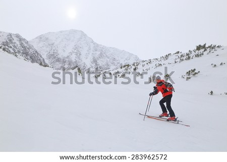 Woman mountaineer struggles to climb on touring skis under harsh weather - stock photo