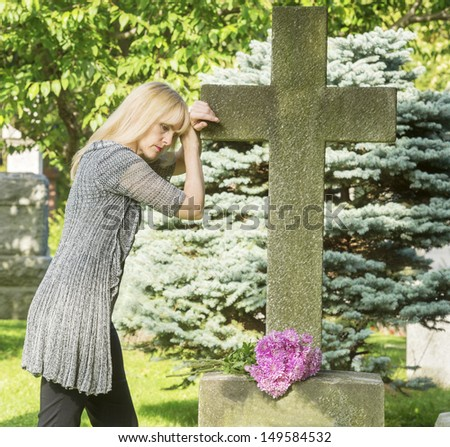 Woman mourns in cemetery resting on cross gravestone - stock photo