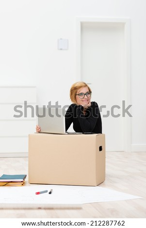 Woman moving home working on a laptop computer balanced on top of a cardboard packing carton - stock photo