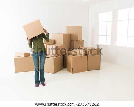 woman moving in new house, having fun hiding her head in cardboard box - stock photo