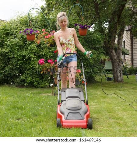 Woman mowed grass in a flower garden - stock photo