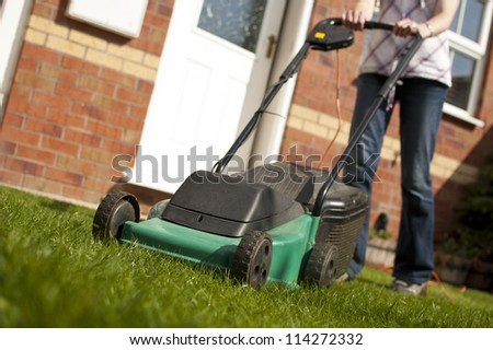 Woman mowing lawn in residential back garden on sunny day - stock photo