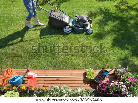 Woman mowing with lawn mower in the garden, gardening concept  - stock photo