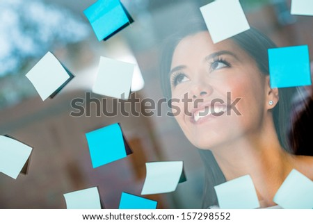 Woman multitasking with posting post-its all over the place - stock photo