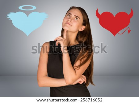 Woman musing between angel and devil hearts. On gray background - stock photo