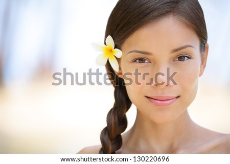 Woman natural beauty portrait of a beautiful and smiling brunette smiling outdoors with a flower in her braided hair. Multicultural Asian / Caucasian girl on health spa wellness travel resort - stock photo