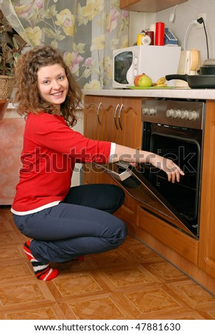 woman near contemporary kitchen oven - stock photo