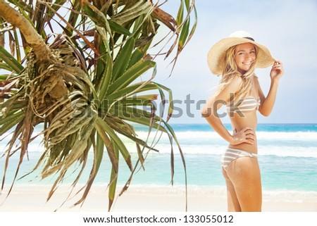 woman near palms on tropical beach - stock photo