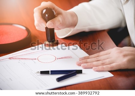 Woman Notary Public stamping the contract. Law office. - stock photo