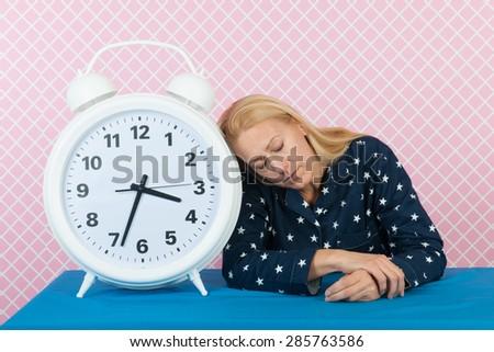Woman of mature age laying next to big alarm clock - stock photo