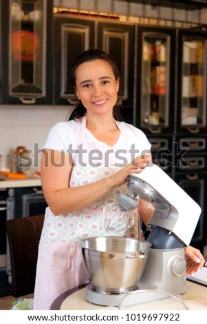 Woman of middle age standing at the kitchen with a food processor.