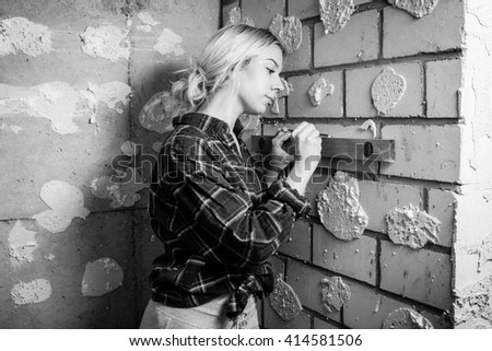 woman of the side measirung indoors a wall with a yellow spirit level