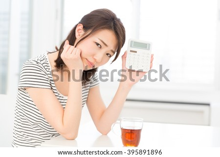 Woman of thinking having an electronic calculator