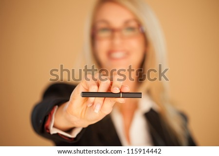 Woman offering a cigarette which she is holding out in her extended hand with selective focus to the cigarette - stock photo
